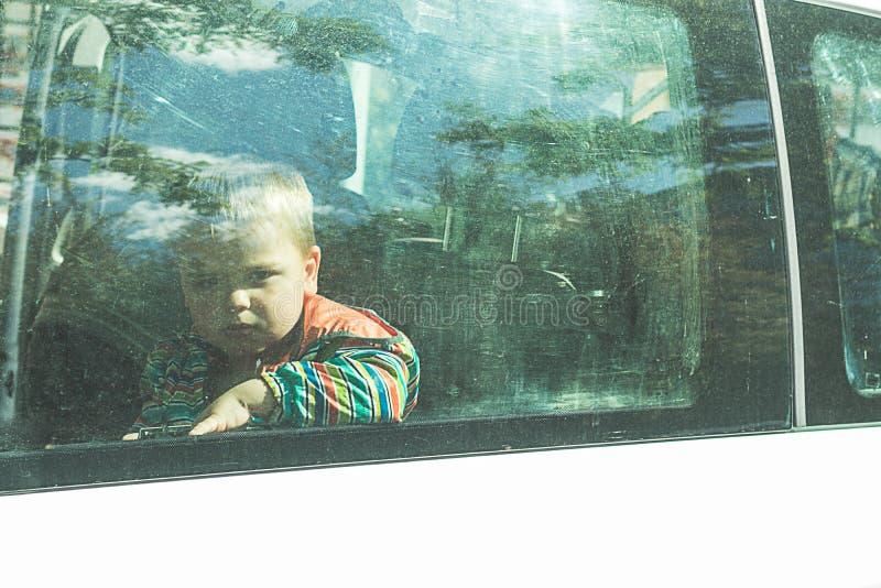 Niño a través de una ventanilla del coche fotografía de archivo