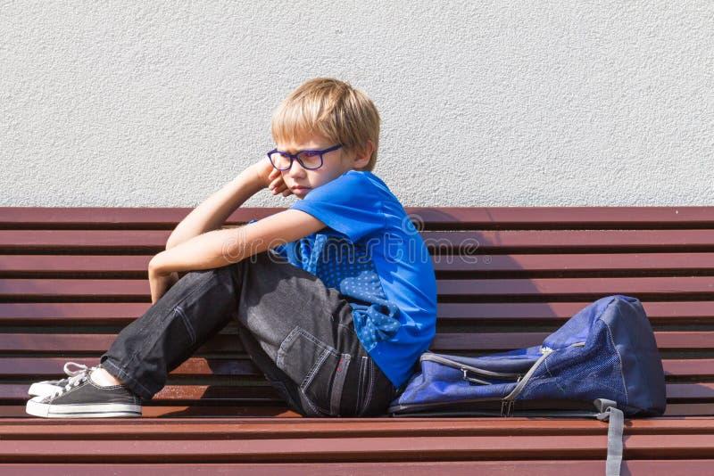 Niño triste, cansado que se sienta solamente en el banco al aire libre fotos de archivo