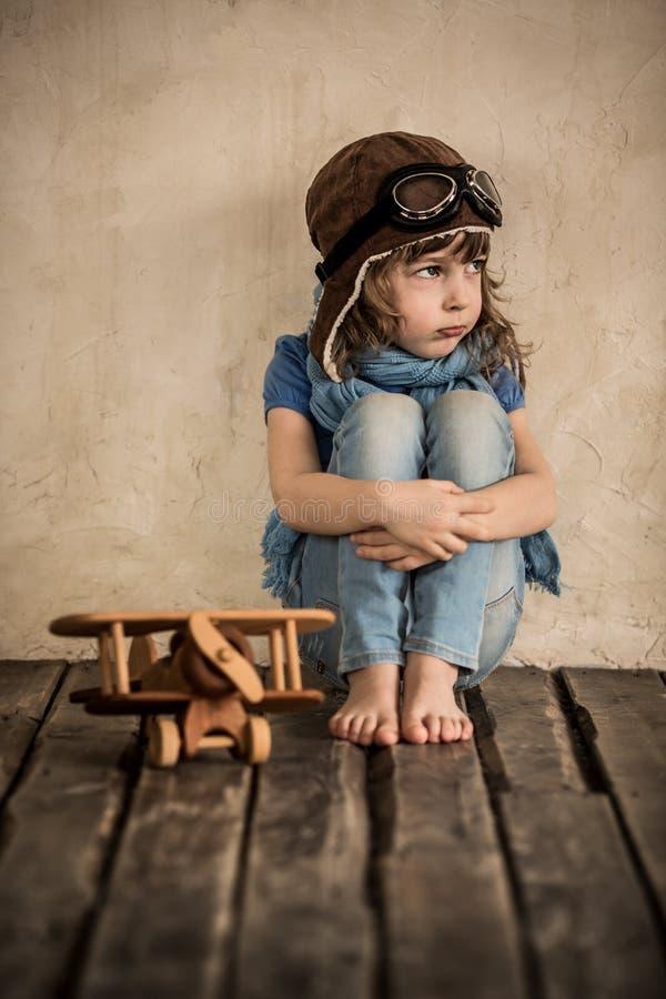 Niño triste con el aeroplano de madera del juguete imágenes de archivo libres de regalías