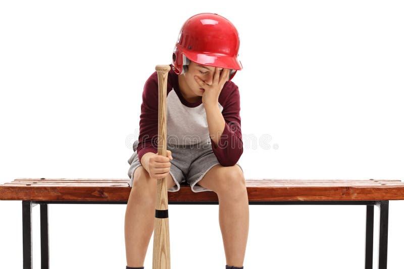 Niño triste con el bate de béisbol que lleva a cabo su cabeza con incredulidad imágenes de archivo libres de regalías
