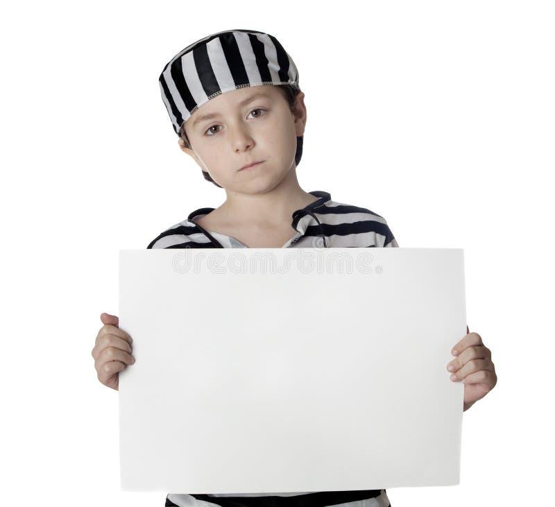Niño triste con el traje del preso y el cartel en blanco imagenes de archivo