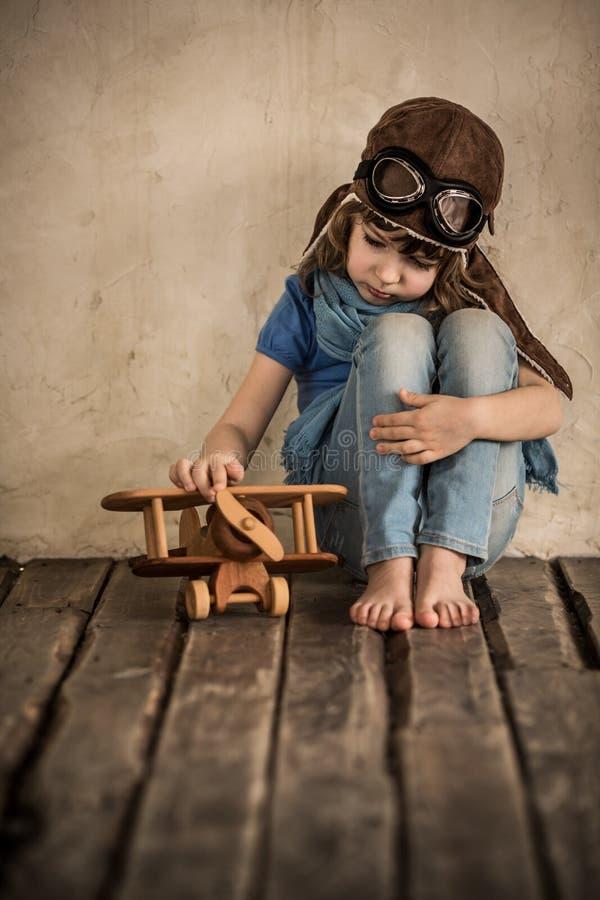 Niño triste que juega con el aeroplano imagenes de archivo