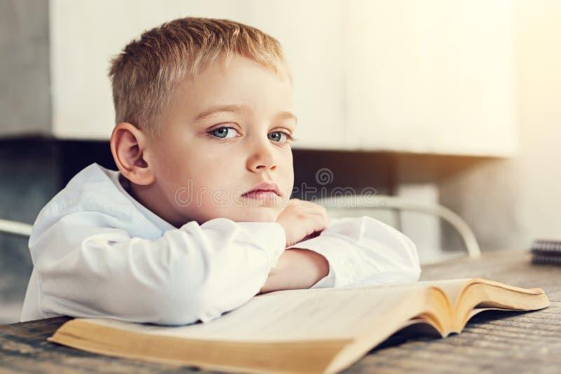 Niño triste que se sienta con un libro imagen de archivo libre de regalías