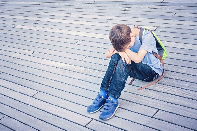 Niño triste, solo, infeliz, decepcionado que se sienta solamente en la tierra al aire libre imagen de archivo libre de regalías