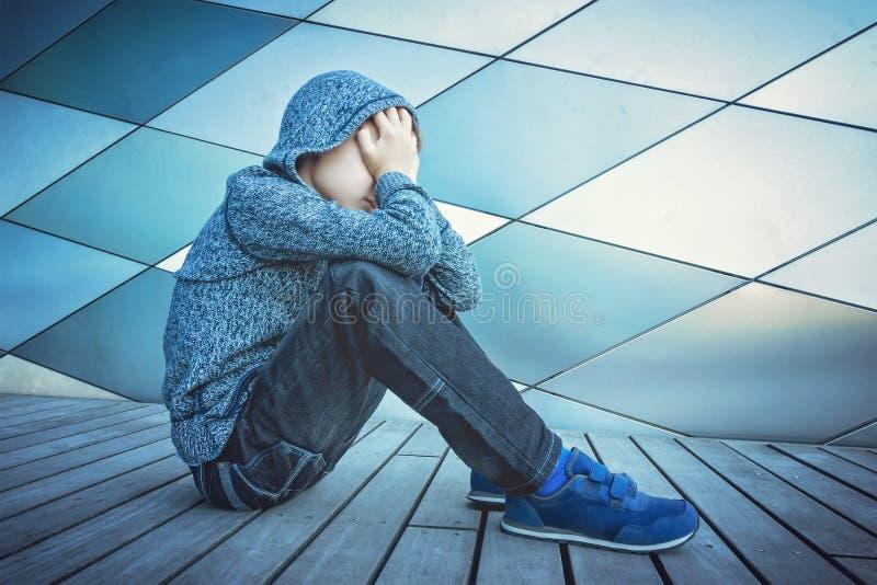 Niño triste, solo, infeliz, decepcionado que se sostiene principal con las manos que se sientan solamente en la tierra al aire li fotografía de archivo libre de regalías