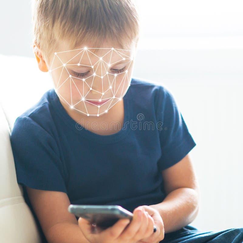 Niño usando el reconocimiento de la identificación de la cara Muchacho con un artilugio del smartphone Concepto nativo de los niñ fotos de archivo