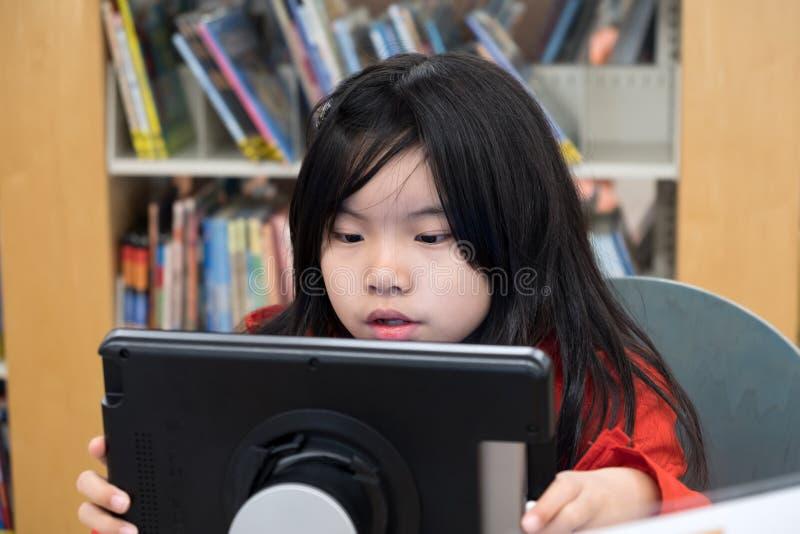 Niño usando la tableta digital en biblioteca imagen de archivo