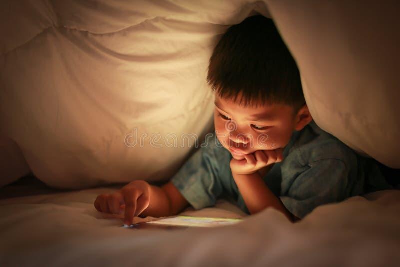 Niño usando la tableta para la historieta en línea del reloj imagenes de archivo