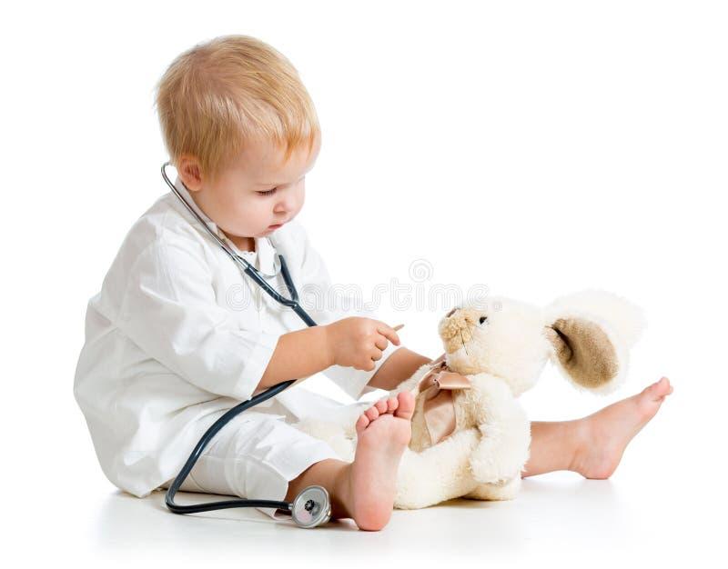 Niño vestido como doctor que juega con el juguete imagenes de archivo