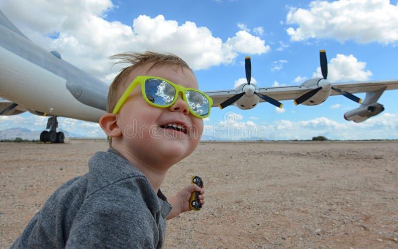 Niño y aeroplano emocionados en el aeropuerto imagenes de archivo