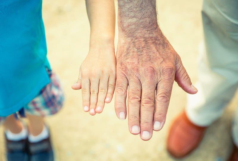 Niño y hombre mayor que comparan su tamaño de las manos imagen de archivo