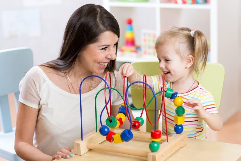 Niño y madre que juegan así como el juguete educativo en cuarto de niños imágenes de archivo libres de regalías