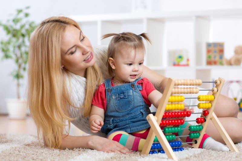Niño y madre que juegan con el ábaco imágenes de archivo libres de regalías