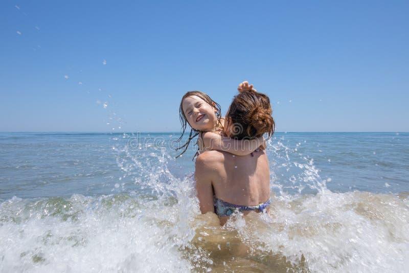 Niño y madre que juegan con las ondas en playa foto de archivo