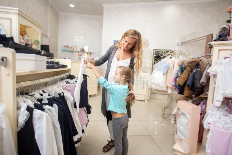 Niño y mujer en una tienda del ` s de los niños imagenes de archivo