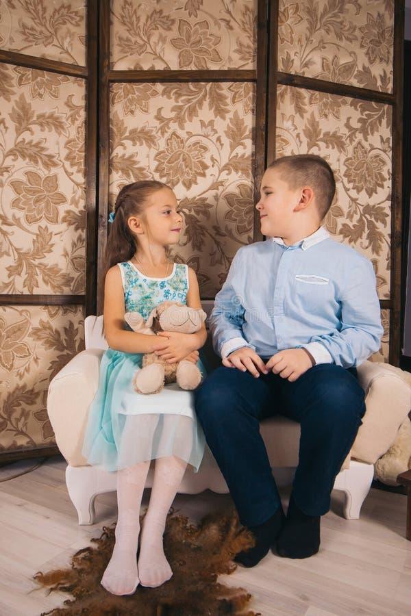 niño y niña sentados en el sofá de la habitación de los niños y mirándose el uno al otro imagen de archivo libre de regalías