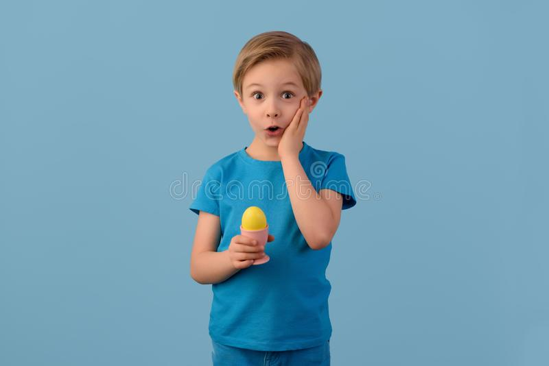 Niño y Pascua El muchacho rubio sonriente, 6 años, está sosteniendo un huevo amarillo en su mano imagen de archivo