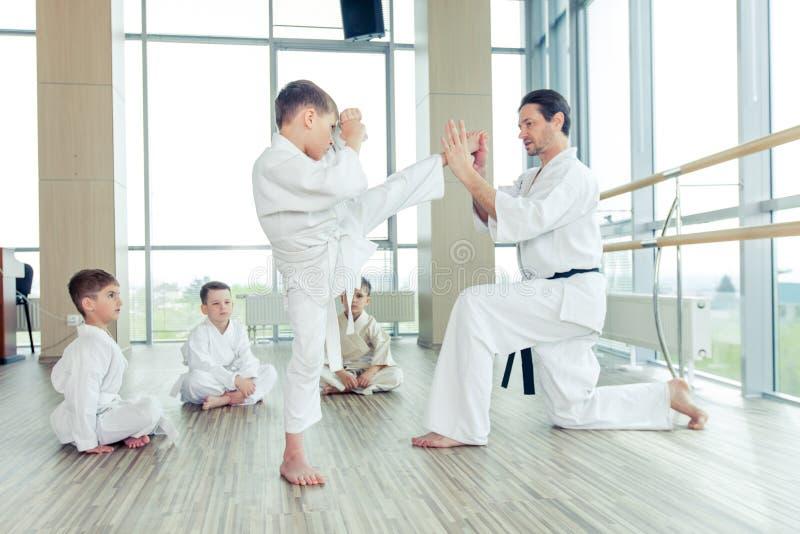 Niños éticos multi jovenes, hermosos, acertados en positi del karate foto de archivo