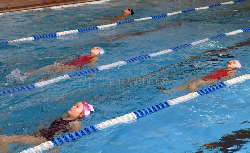 Niños 8 años, aprendiendo nadar en piscina de revestimiento. foto de archivo