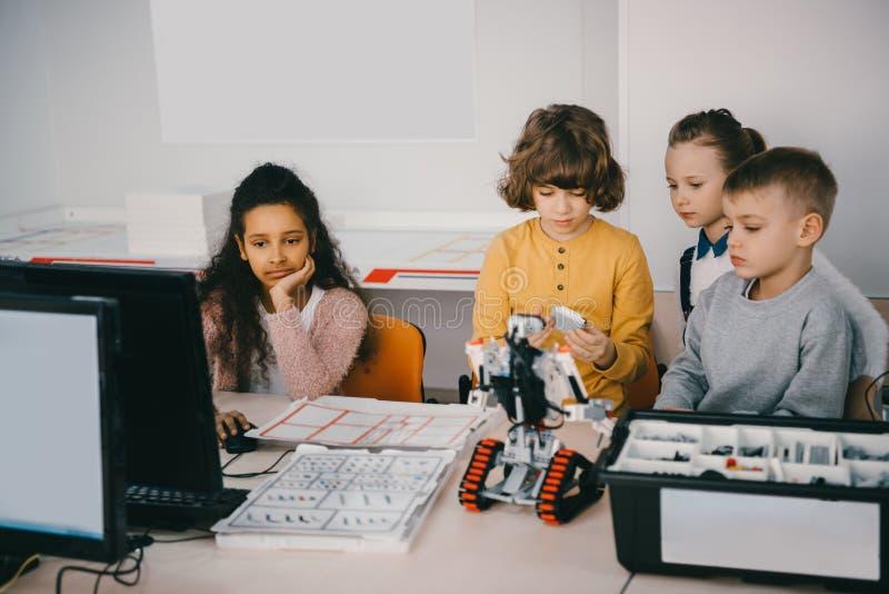 niños adolescentes enfocados que construyen el robot diy imagenes de archivo