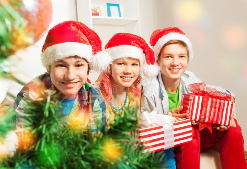 Niños adolescentes lindos con los presentes por el árbol de navidad fotos de archivo libres de regalías
