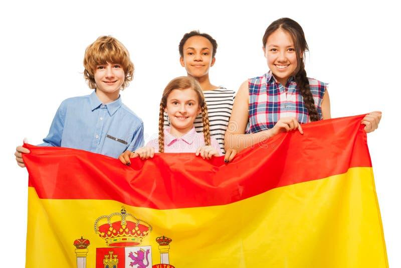 Niños adolescentes multiétnicos felices con la bandera de España imagen de archivo libre de regalías