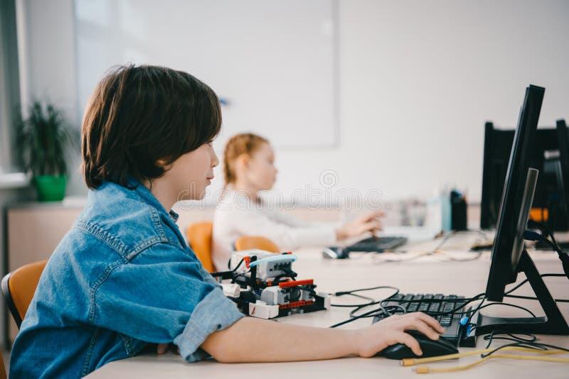 niños adolescentes que trabajan junto en la clase de la maquinaria, tronco fotos de archivo libres de regalías