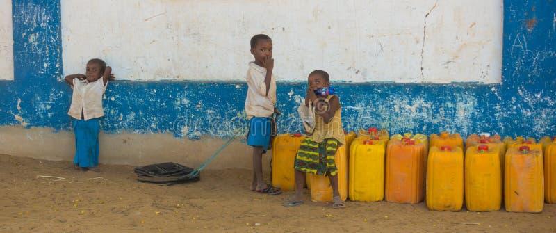 Niños africanos del pueblo en envases de la naranja de Kenia imagen de archivo