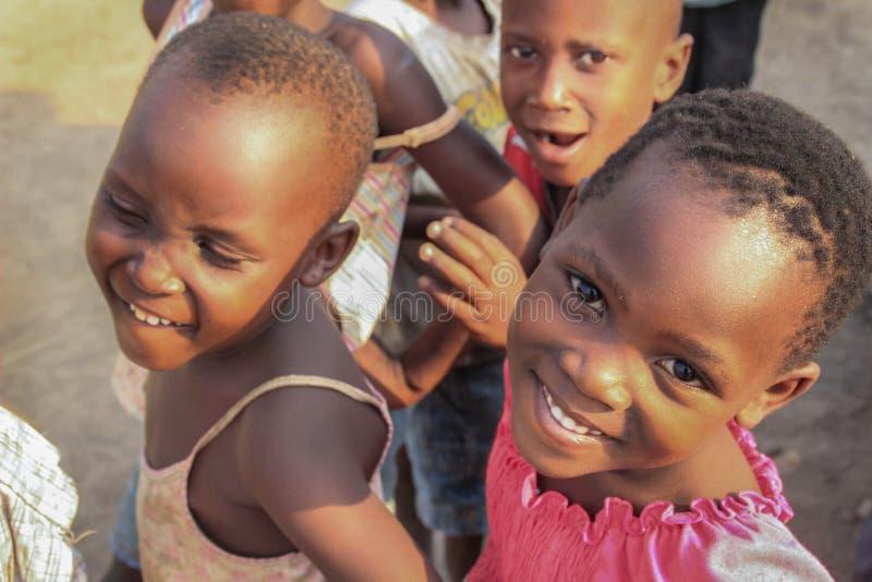 Niños africanos del pueblo que juegan cerca de la orilla del lago en el suburbio de Fort Portal imágenes de archivo libres de regalías
