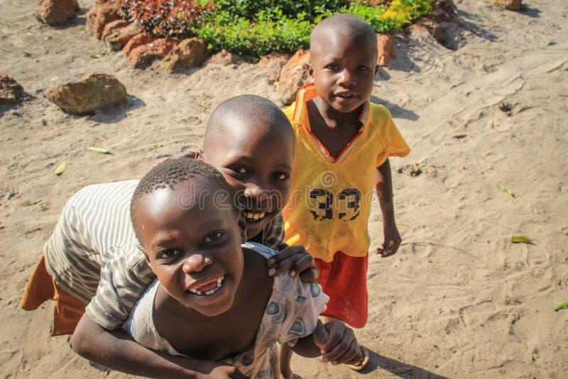 Niños africanos del pueblo que juegan cerca de la orilla del lago en el suburbio de Fort Portal fotografía de archivo