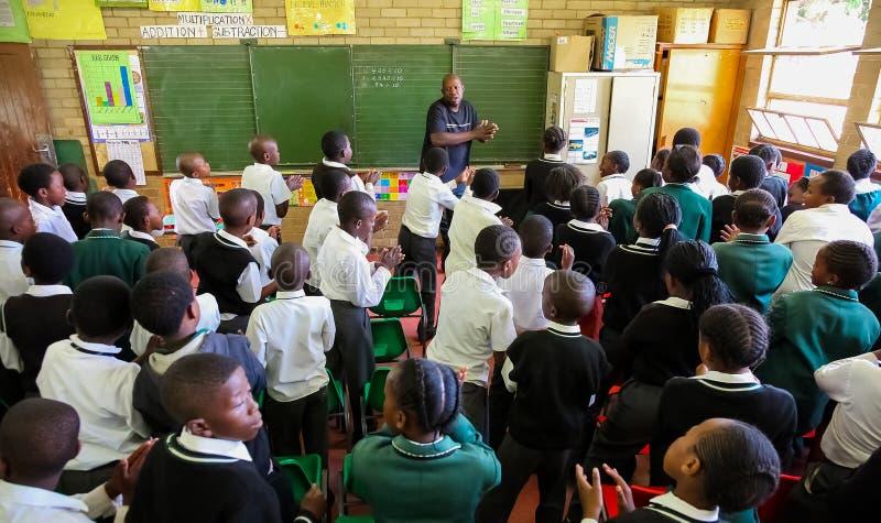 Niños africanos en sala de clase de la escuela primaria fotografía de archivo