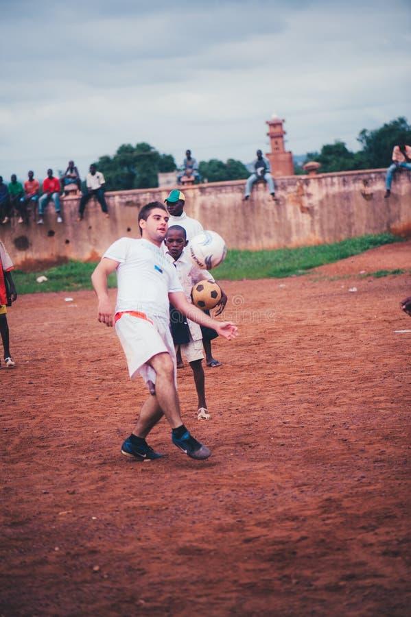 Niños africanos negros, muchachos y adultos jugando a fútbol con los voluntarios caucásicos foto de archivo libre de regalías