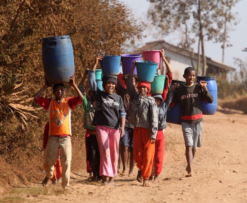 Niños africanos que llevan el agua fotos de archivo