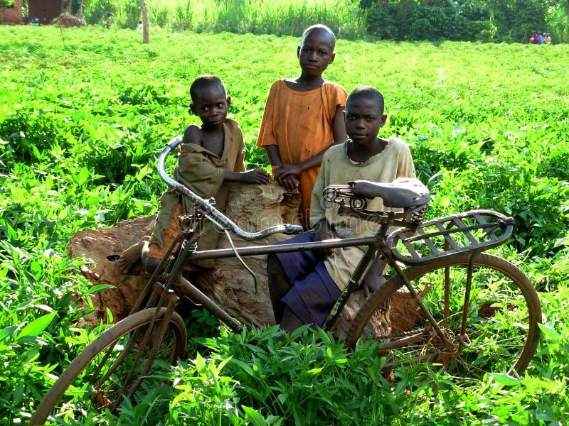 Niños africanos que se colocan en los arbustos con su bici fotos de archivo libres de regalías