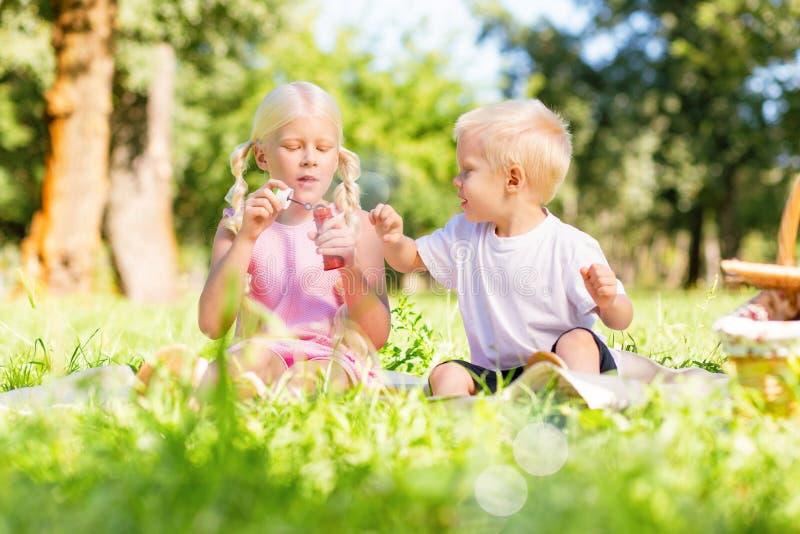 Niños agradables que juegan junto en el parque imagen de archivo
