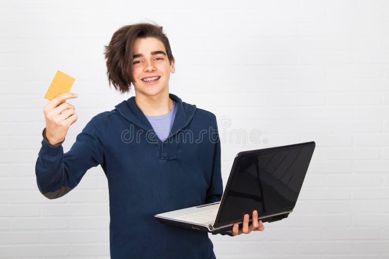 Niños aislados con ordenador portátil y tarjeta de crédito foto de archivo libre de regalías