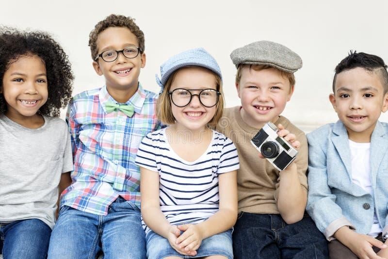 Niños alegres casuales que se sientan al gether imagenes de archivo