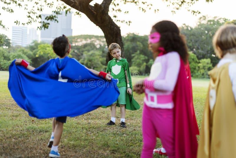 Niños alegres de los super héroes que expresan concepto de la positividad fotografía de archivo