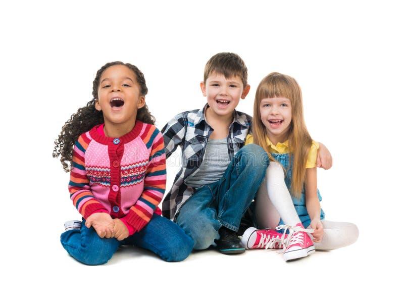 Niños alegres de Thre que se sientan en el piso en un estudio foto de archivo
