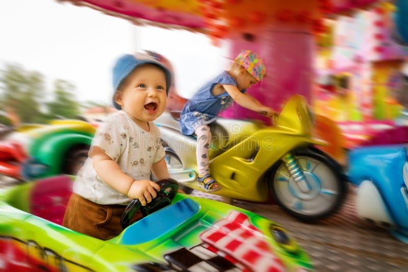 Niños alegres en carrusel en el parque de atracciones foto de archivo