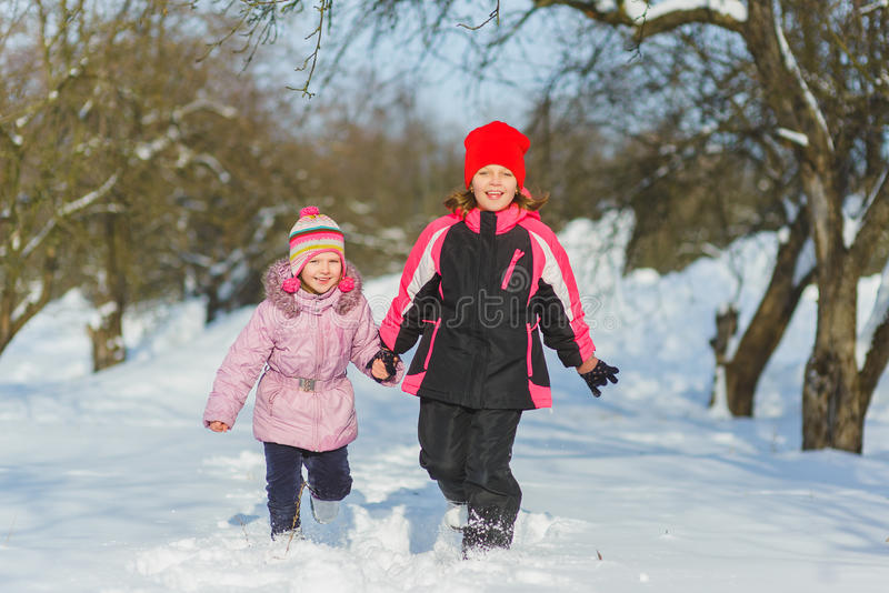 Niños alegres que juegan en nieve Dos muchachas felices que se divierten fuera del día de invierno foto de archivo libre de regalías