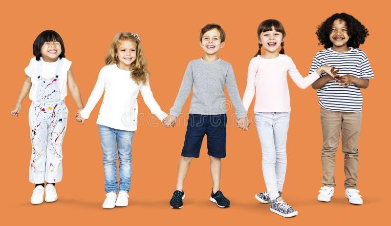 Niños alegres que llevan a cabo las manos aisladas en fondo fotografía de archivo