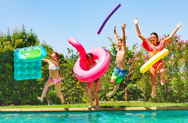 Niños alegres que se divierten durante la fiesta en la piscina del verano imagen de archivo