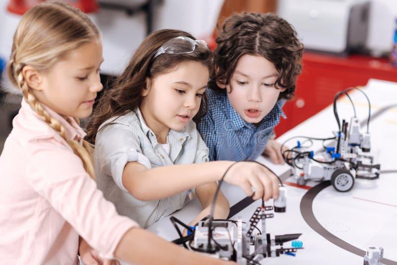 Niños animados que discuten proyecto en la escuela imagen de archivo