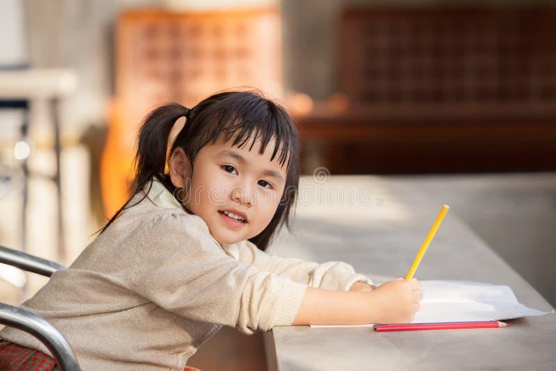 Niños asiáticos con el lápiz amarillo a disposición que hace el trabajo del hogar de la escuela imágenes de archivo libres de regalías