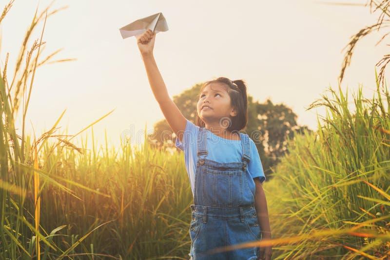 niños asiáticos lindos que juegan el aeroplano de papel en el campo del arroz imágenes de archivo libres de regalías
