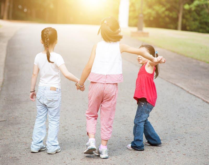 Niños asiáticos que celebran caminar de las manos al aire libre imagen de archivo