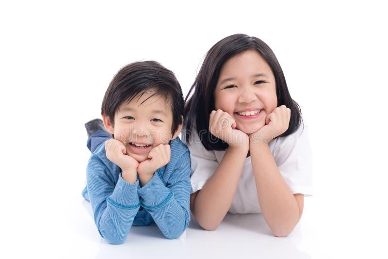 Niños asiáticos que mienten en el fondo blanco aislado imagen de archivo