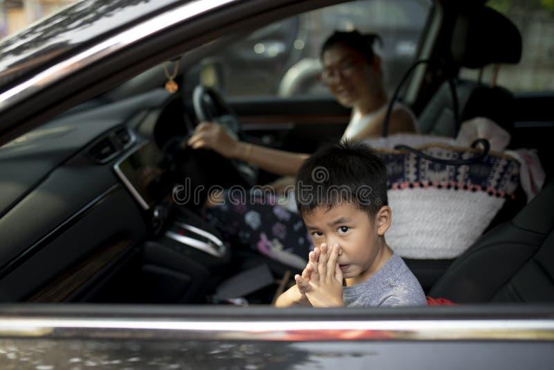 Niños asiáticos que se sientan en asiento de pasajero e ir a enseñar con la madre imagen de archivo libre de regalías