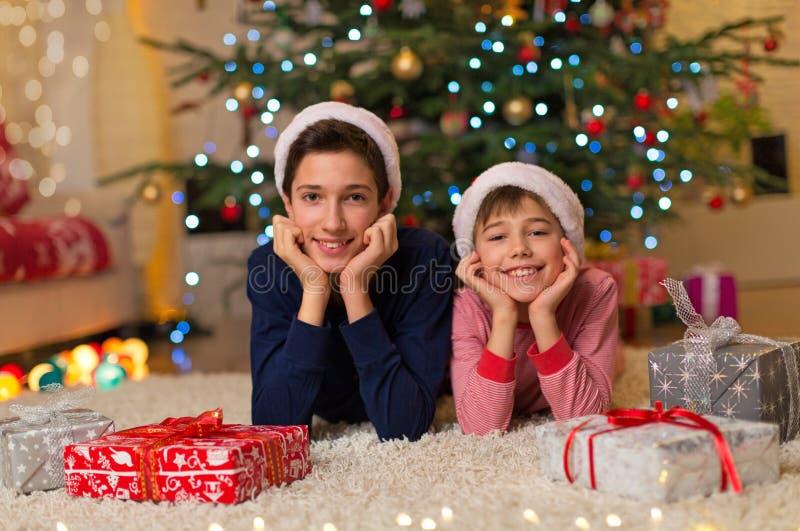 Niños bajo el árbol de navidad imagen de archivo libre de regalías
